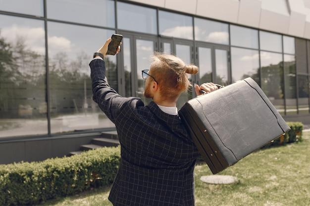 Geschäftsmann mit koffer, der in einer sommerstadt geht