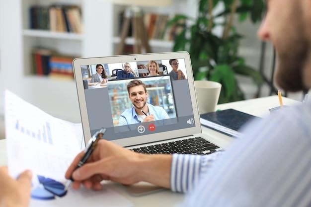 Geschäftsmann mit kopfhörern im gespräch mit ihren kollegen in videokonferenz