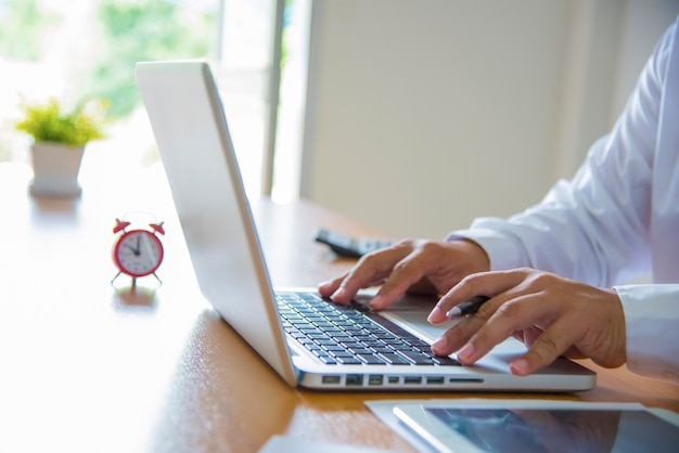 Geschäftsmann mit laptop-computer. männliche hand eingabe auf laptop-tastatur