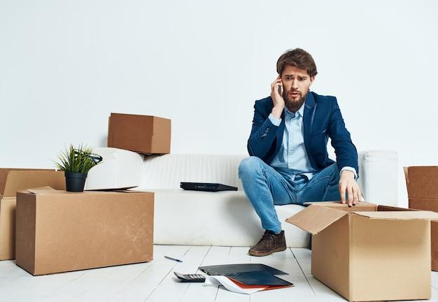 Geschäftsmann mit laptop, der auf sofa sitzt, das kisten offiziell auspackt