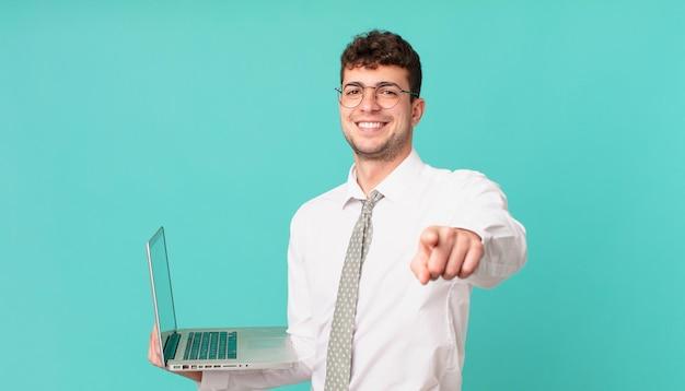 Geschäftsmann mit laptop, der mit einem zufriedenen, selbstbewussten, freundlichen lächeln auf die kamera zeigt und sie wählt