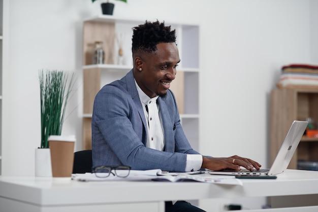 Geschäftsmann mit laptop. junger afrikanischer geschäftsmann tippt etwas auf laptop in seinem büro.