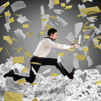 Geschäftsmann mit laptop läuft vor papierkram und bürokratie davon