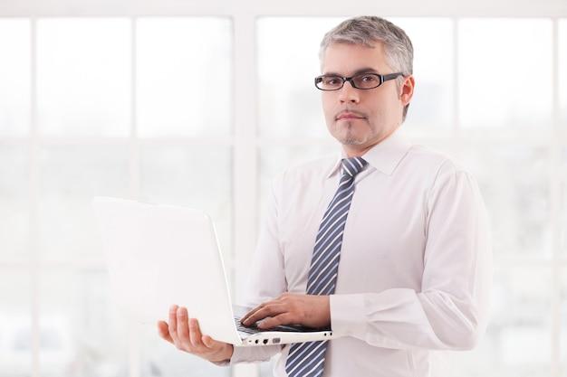 Geschäftsmann mit laptop. selbstbewusster älterer mann in hemd und krawatte, der laptop hält und in die kamera schaut
