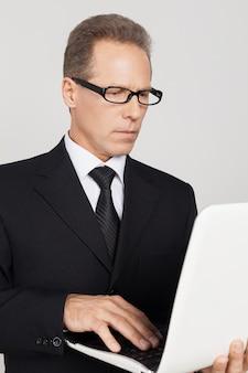 Geschäftsmann mit laptop. selbstbewusster reifer mann in abendgarderobe, der am laptop arbeitet, während er vor grauem hintergrund steht