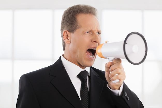 Geschäftsmann mit megaphon. porträt eines selbstbewussten reifen mannes in formeller kleidung, der am megaphon schreit, während er in der nähe des fensters steht