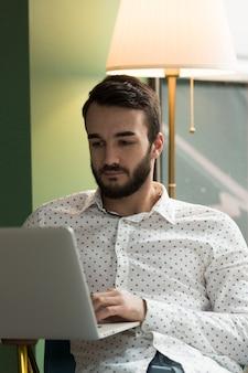 Geschäftsmann mit niedrigem winkel, der am laptop arbeitet