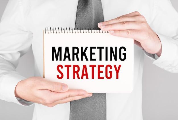 Geschäftsmann mit notizbuch mit text marketingstrategie