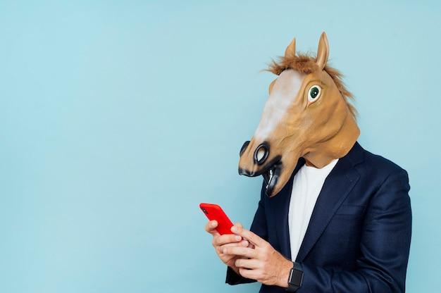 Geschäftsmann mit pferdemaske mit smartphone