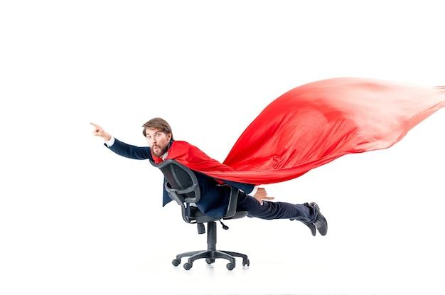 Geschäftsmann mit rotem mantel, der im superman-bürostuhl versucht