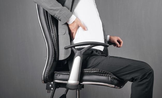 Geschäftsmann mit rückenschmerzen im bürostuhl sitzen.