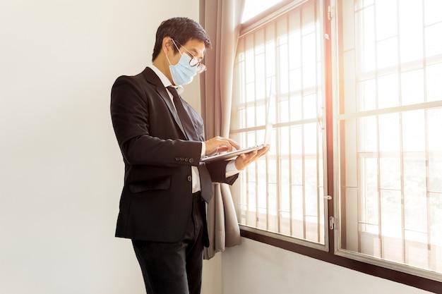 Geschäftsmann mit schutzmaske, die am laptop zu hause arbeitet.