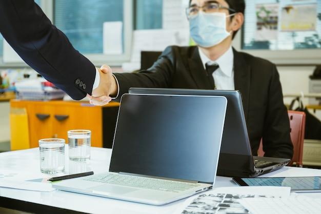 Geschäftsmann mit schutzmaske handschlag erfolgreiche vereinbarung