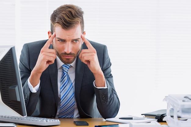 Geschäftsmann mit schweren kopfschmerzen am schreibtisch