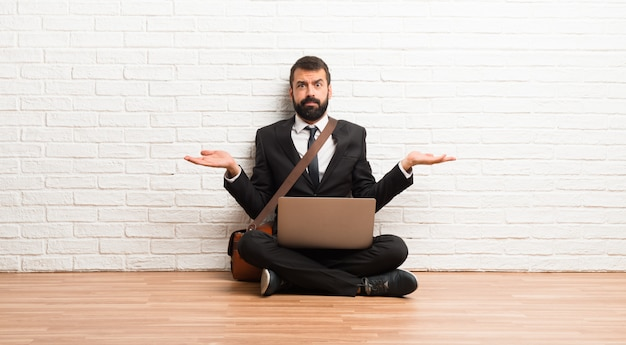 Geschäftsmann mit seinem laptop auf dem boden sitzen unglücklich und mit etwas frustriert, weil etwas nicht verstehen