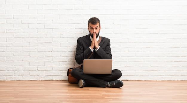 Geschäftsmann mit seinem laptop auf dem boden sitzend hält palme zusammen. person bittet um etwas
