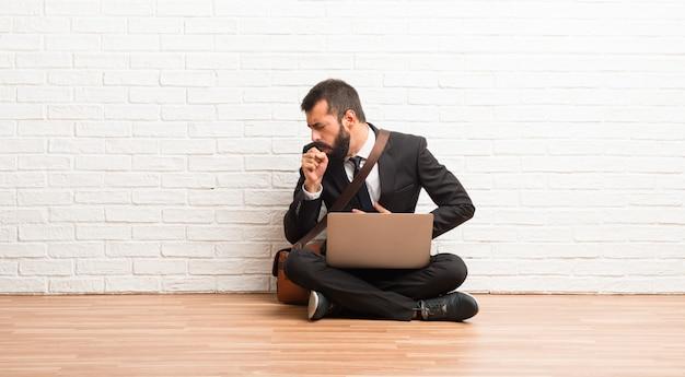 Geschäftsmann mit seinem laptop auf dem boden sitzend leidet mit husten und fühlt sich schlecht
