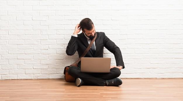 Geschäftsmann mit seinem laptop, der auf dem boden auf der hinteren position zurück schaut beim verkratzen des kopfes sitzt