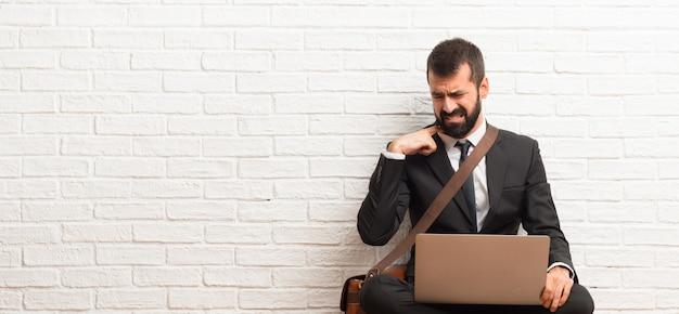 Geschäftsmann mit seinem laptop, der auf dem boden mit müdem und krankem ausdruck sitzt