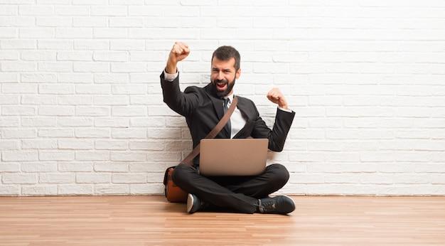 Geschäftsmann mit seinem laptop, der auf dem boden sitzt, einen sieg feiernd und überrascht, erfolgreich zu sein
