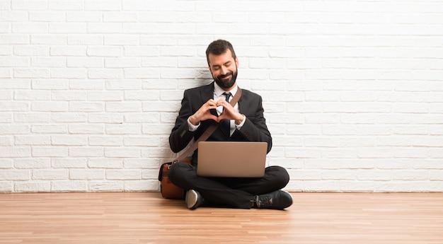 Geschäftsmann mit seinem laptop, der auf dem boden sitzt, herzsymbol durch hände machend