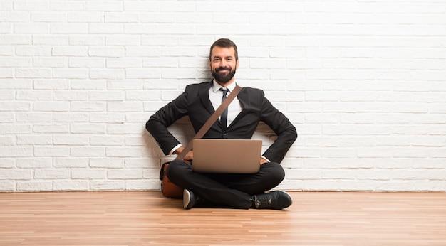 Geschäftsmann mit seinem laptop, der auf dem boden sitzt mit den armen an der hüfte und am lächeln sitzt