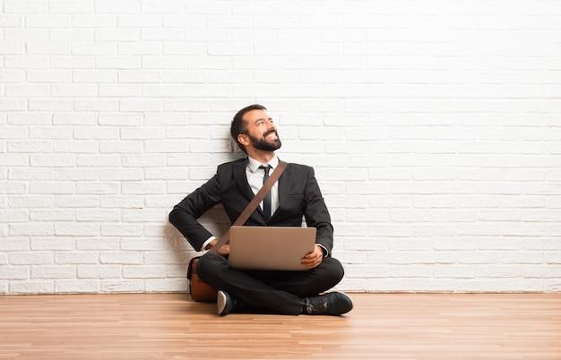 Geschäftsmann mit seinem laptop, der auf dem boden sitzt mit den armen an der hüfte und lachen sitzt