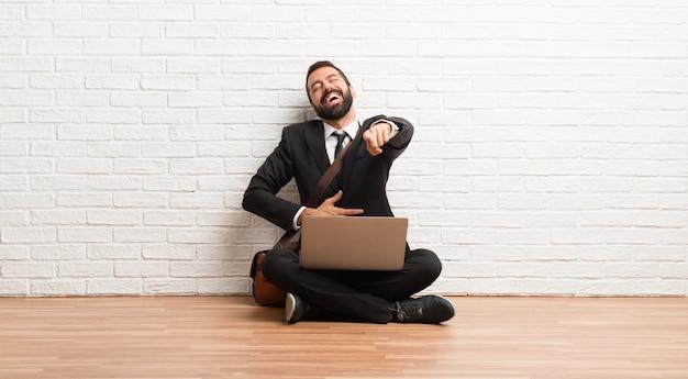 Geschäftsmann mit seinem laptop, der auf dem boden sitzt mit finger auf jemand zeigend und viel lacht