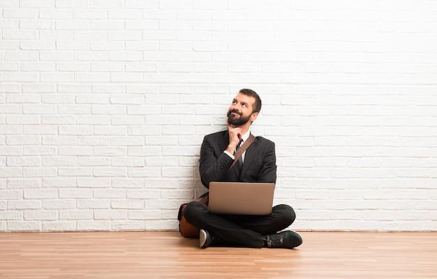 Geschäftsmann mit seinem laptop, der auf dem boden sitzt und eine idee beim oben schauen sitzt und denkt