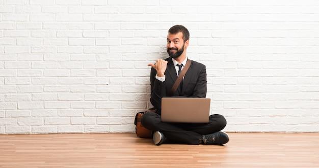 Geschäftsmann mit seinem laptop, der auf dem boden sitzt, zeigend auf die seite mit einem finger, um ein produkt darzustellen