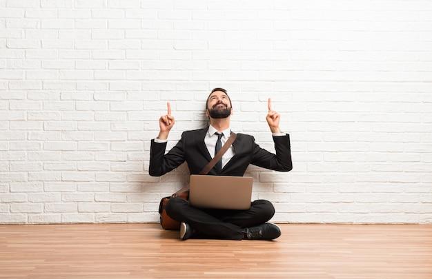 Geschäftsmann mit seinem laptop, der auf dem boden sitzt, zeigend mit dem zeigefinger eine großartige idee