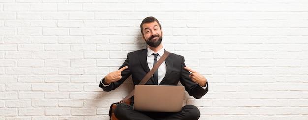 Geschäftsmann mit seinem laptop, der auf dem boden stolz und in konzept der liebe selbst zufrieden sitzt