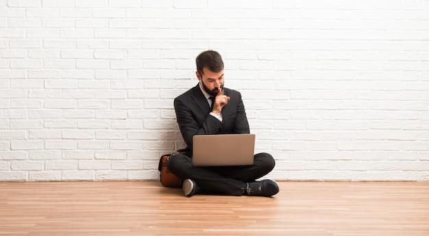 Geschäftsmann mit seinem laptop, der auf dem boden zeigt ein zeichen des schließenden munds und der ruhegeste sitzt
