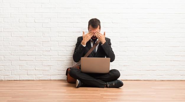 Geschäftsmann mit seinem laptop, der auf dem bodenbelag sitzt, mustert durch hände. überrascht zu sehen, was vor uns liegt