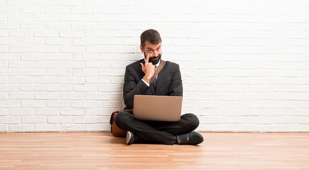 Geschäftsmann mit seinem laptop, der auf dem fußboden schaut zur front sitzt