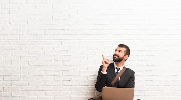 Geschäftsmann mit seinem laptop, der auf dem fußboden sitzt, eine großartige idee zeigend und oben schauend