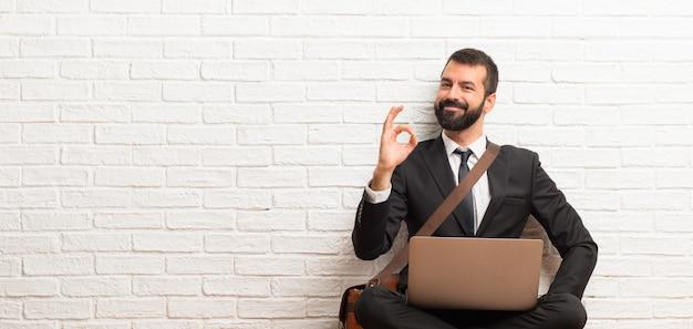 Geschäftsmann mit seinem laptop, der auf dem fußboden zeigt ein okayzeichen mit den fingern sitzt