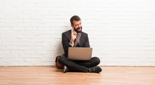Geschäftsmann mit seinem laptop, der auf dem fußboden zeigt okayzeichen beim blinzeln eines auges sitzt