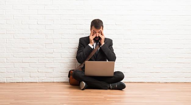 Geschäftsmann mit seinem laptop, der auf dem überraschten boden sitzt und gesicht mit den händen beim schauen durch finger bedeckt