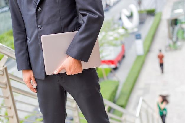 Geschäftsmann mit seinem laptop, der die treppe in einer hauptverkehrszeit hinaufgeht, um zu arbeiten. beeil dich mal