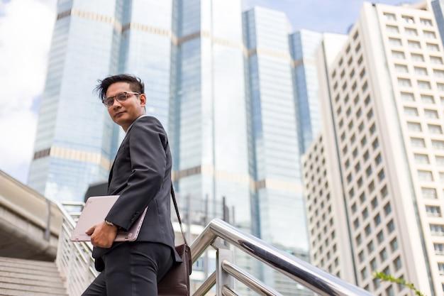 Geschäftsmann mit seinem laptop, der die treppe in einer hauptverkehrszeit hinaufgeht, um zu arbeiten. beeilen sie sich.