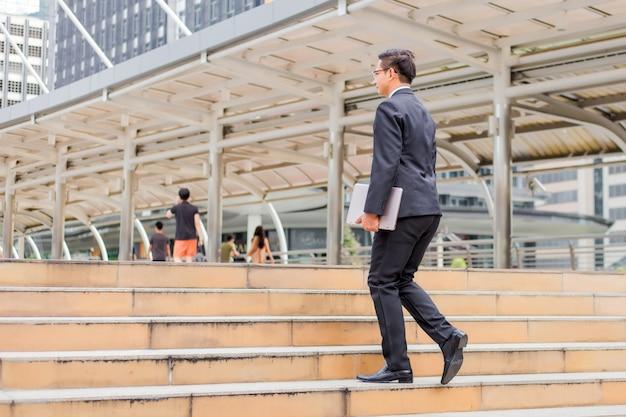 Geschäftsmann mit seinem laptop, der die treppe in einer hauptverkehrszeit hinaufgeht, um zu arbeiten