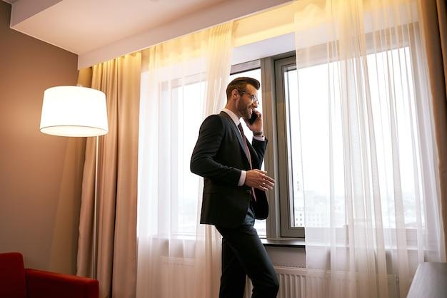 Geschäftsmann mit smartphone, der am fenster im hotelzimmer steht