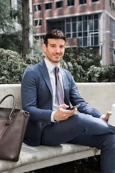 Geschäftsmann mit smartphone und getränk