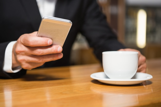 Geschäftsmann mit smartphone und kaffee trinken