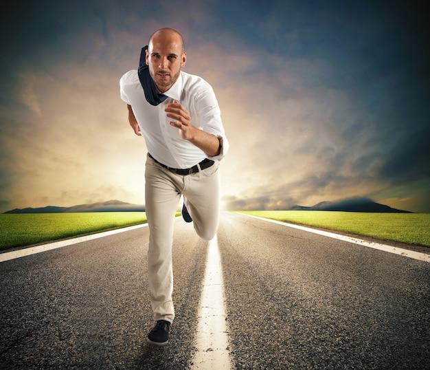 Geschäftsmann mit tasche geht bei ankunft eines rennens über das rote band hinaus