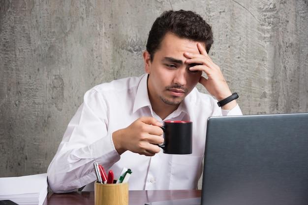 Geschäftsmann mit tasse tee, der sich am schreibtisch müde fühlt. hochwertiges foto