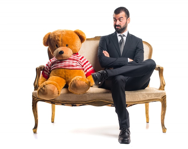 Geschäftsmann mit teddy sitzt auf vintage-sessel