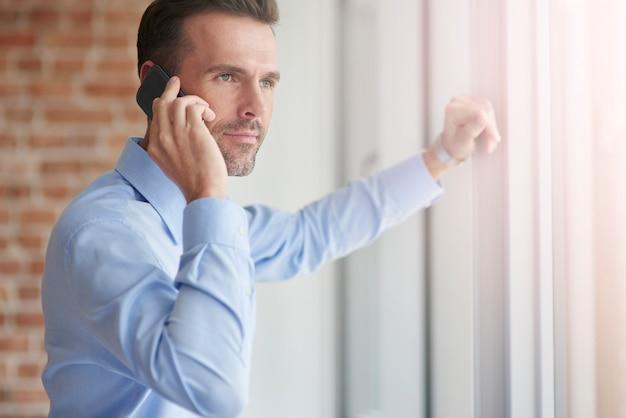Geschäftsmann mit telefon, das an das fenster lehnt
