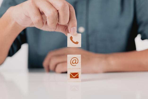 Geschäftsmann mit telefon-e-mail und adresse auf einem holzblock-würfelsymbol